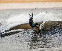 Riding the wakeboard over an artificial wave